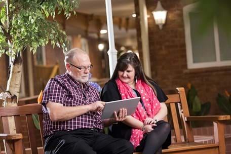 Photo of a woman and man on a bench looking at a laptop.